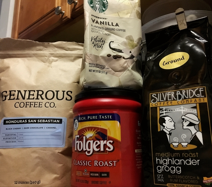 Packages of Generous Coffee Co coffee, Starbucks vanilla coffee, Folger's and Silver Bridge Coffee