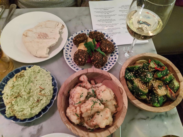 Tabletop with glass of white wine, brussels sprouts, pita bread, falafel, crispy cauliflower, and whipped feta and pistachio dip
