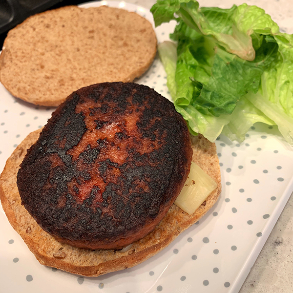 Trader Joe's Protein Patty on a multigrain bun on a white polka dot plate with lettuce